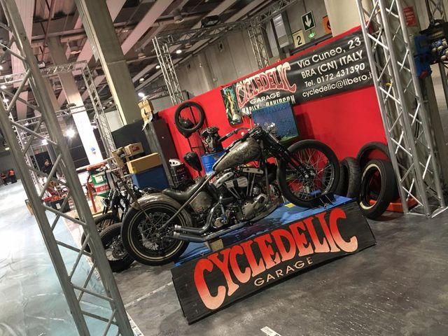 delle moto chopper parcheggiate in officina e uno striscione con scritto Cycledelic Garage