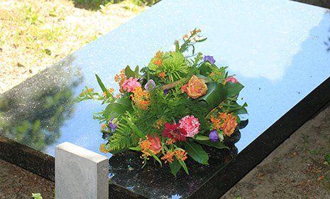 Semplice bouquet di rose e altri fiori su una tomba di marmo nero lisa