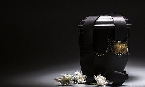 Urna in colore nero con dettagli dorato e fiori bianche al lato