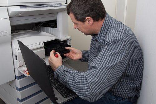 un uomo chinato a terra che ripara una fotocopiatrice