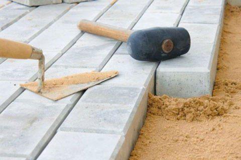 una paletta un martello di gomma e delle mattonelle in marmo