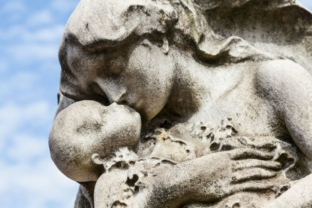 una statua di una donna che bacia un bambino