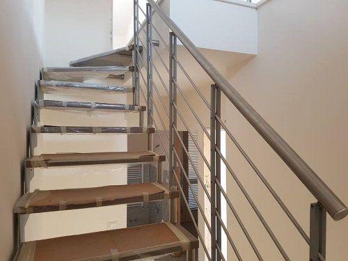 dei gradini in legno e un corrimano in ferro