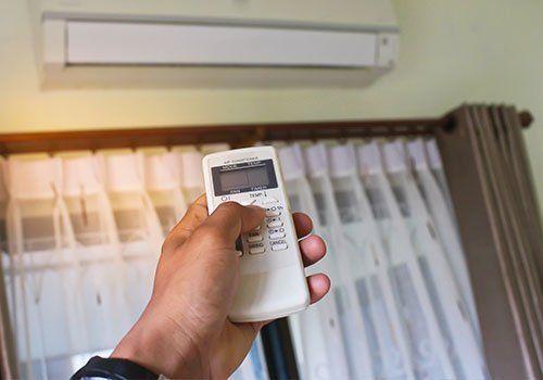 mano con telecomando che attiva impianto di climatizzazione