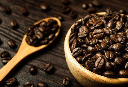 Boll di legno pieno di chicchi di caffè e la benna di legno anche