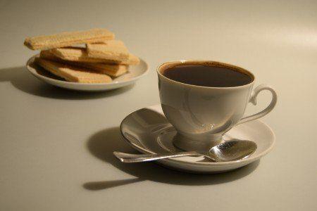 Tazza di caffè e piatto di pastini