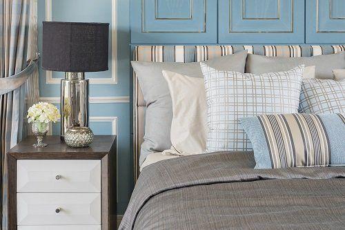 un letto con dei cuscini e un copriletto di color grigio