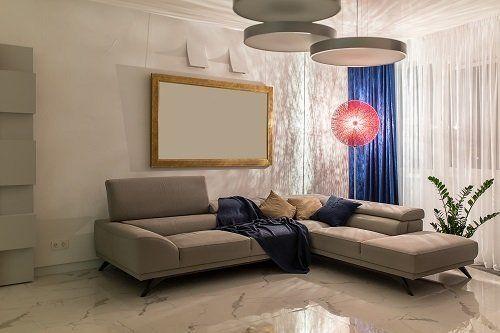 una sala con un divano di color grigio e delle tende di color blu e bianco