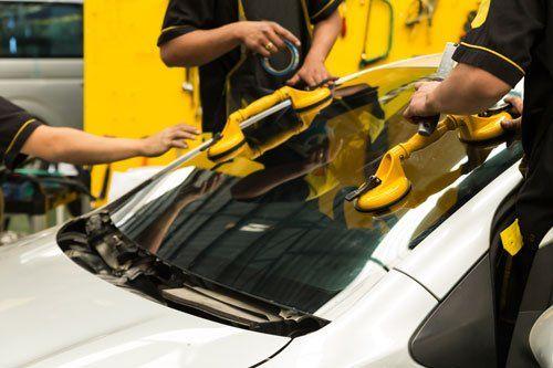 dei carrozzieri che montano un vetro anteriore i una macchina