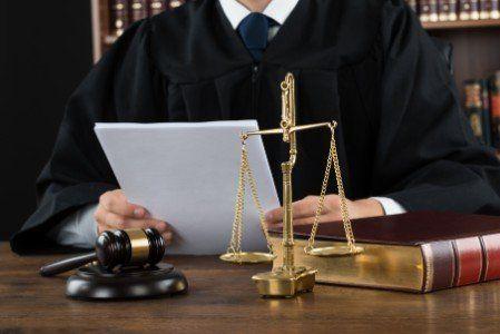 Uomo con toga, libro delle leggi, martello e bilancia della giustizia
