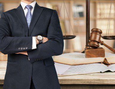 Uomo con abito, martello  e bilancia della giustizia