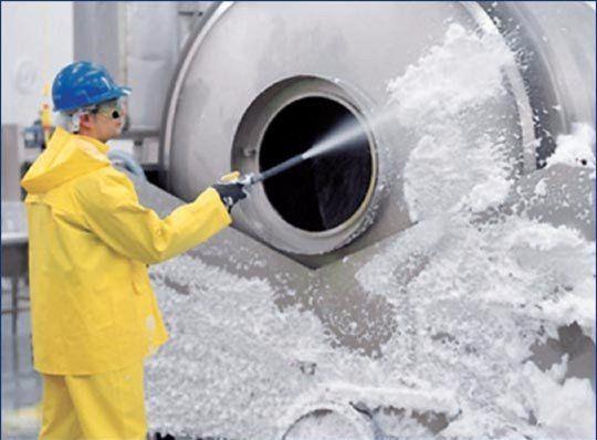 un uomo con una tuta protettiva bianca mentre pulisce con un idropultitrice all'interno di un'industria