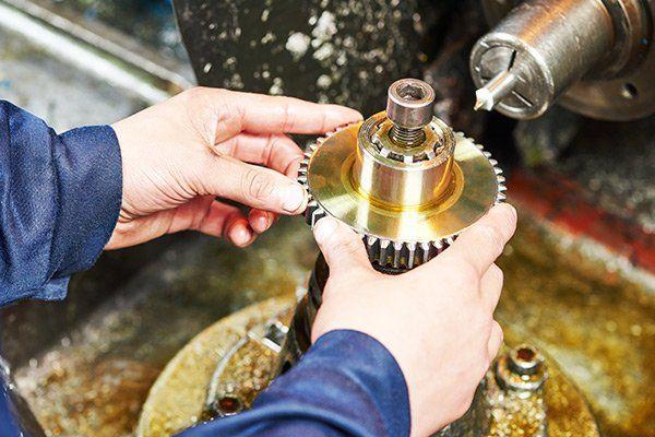 due mani che impugnano un ingranaggio durante una lavorazione
