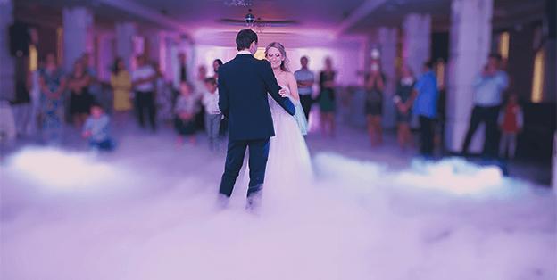 bride and groom dancing on a smoke cloud
