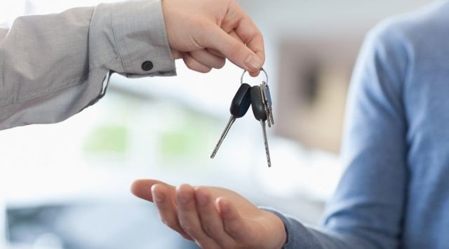 car salesman handing keys over to new car owner