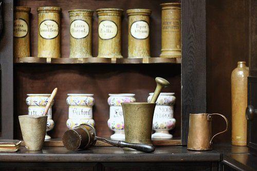mortai in pietra e bronzo e scaffale di contenitori in legno e ceramica