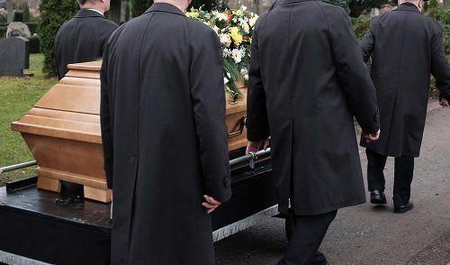 Gruppo trasporta un cofano funebre