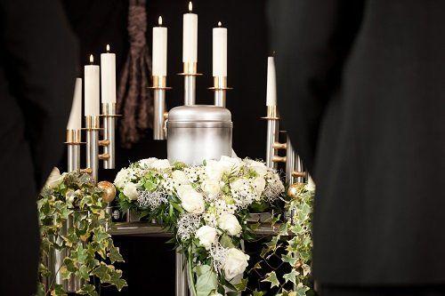 Candelabri e decorazioni floreali durante una celebrazione funebre