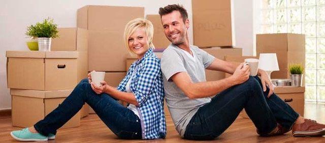 coppia che sorride con delle casse per il trasloco