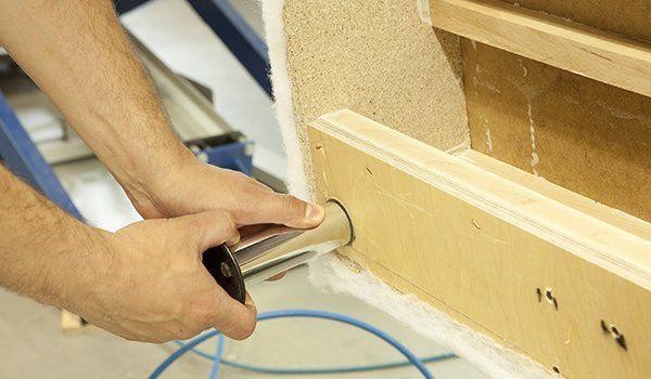 due mani che stanno inserendo un tubo di acciaio in un mobiletto di legno chiaro