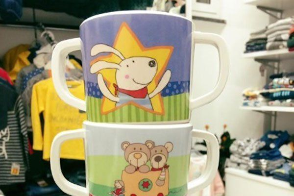 Tre tazze con disegni di cartoni animati appoggiati una sopra l'altra sopra una mensola all'interno di un negozio di abbigliamento