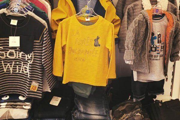 Tre appendiabiti in acciaio con magliette e felpe per bambini di color giallo, blu e grigio e delle mensole con dei jeans piegati