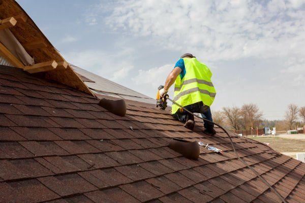 un uomo chinato  al lavoro su un tetto