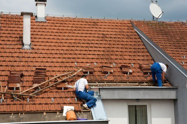 degli uomini al lavoro su un tetto