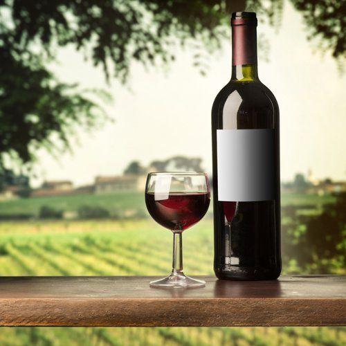 bottiglia e bicchiere di chianti su un tavolo in legno con sfondo toscano