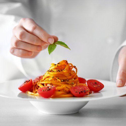 chef mette del basilico su una montagna di spaghetti al pomodoro e pepe