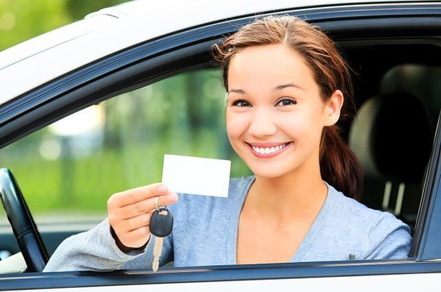 Young woman showing off driving license in Delta