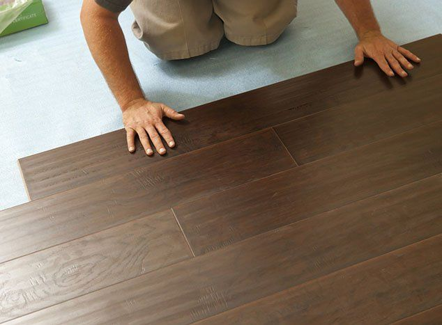 Hardwood Floors Installation — Man Installing New Laminate Wood Flooring in Wooden Floor in Columbus,