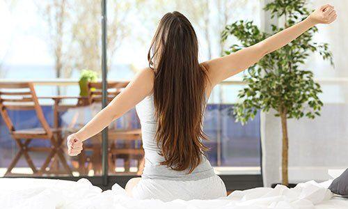 Donna che allunga le braccia dopo essersi svegliata seduta sul letto