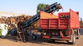 camion rosso che carica legna
