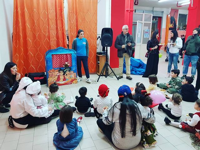 Dei bambini con i genitori seduti sul pavimento e davanti uno spettacolo di pupazzi