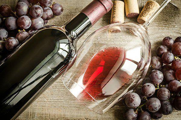 una bottiglia di vino, un bicchiere con del vino rosso e dell'uva nera