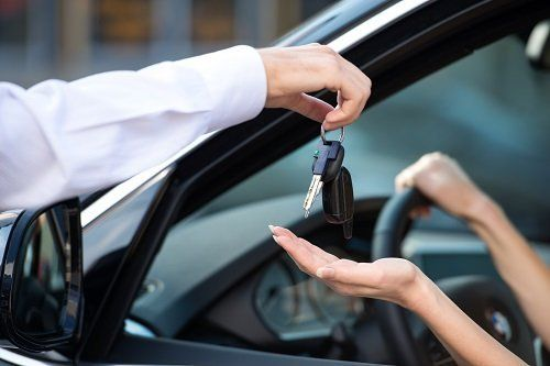una mano che consegna delle chiavi in una mano di una donna in un'auto