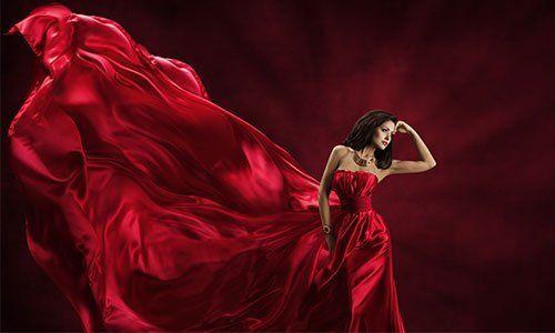una donna con capelli neri e un abito rosso svolazzante molto lungo