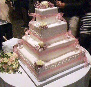 Torta di nozze quadrata di quattro piani abbellita con rose bianche di zucchero e legami rose