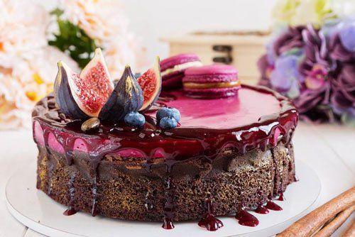 una torta al cioccolato con sopra una confettura rossa, sei macarons francesi rosa e un fico tagliato a spicchi