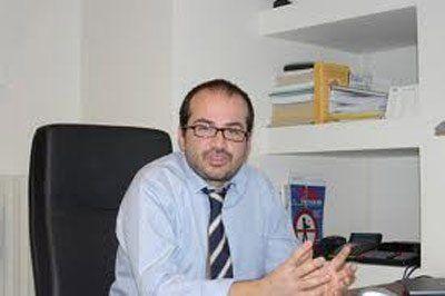 Un signore con gli occhiali seduto alla scrivania mentre posa per una foto