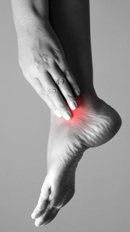 woman holding sore ankle