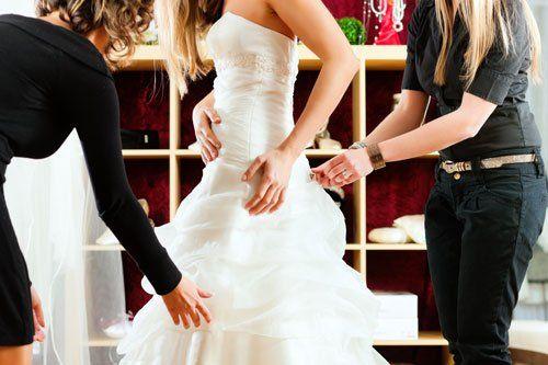 una donna che prova un abito da sposa e accanto altre due donne che la aiutano