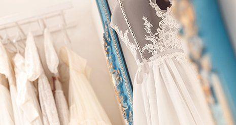 Un manichino con un  abito da sposa di color bianco e in fondo un appendino con degli abiti da sposa