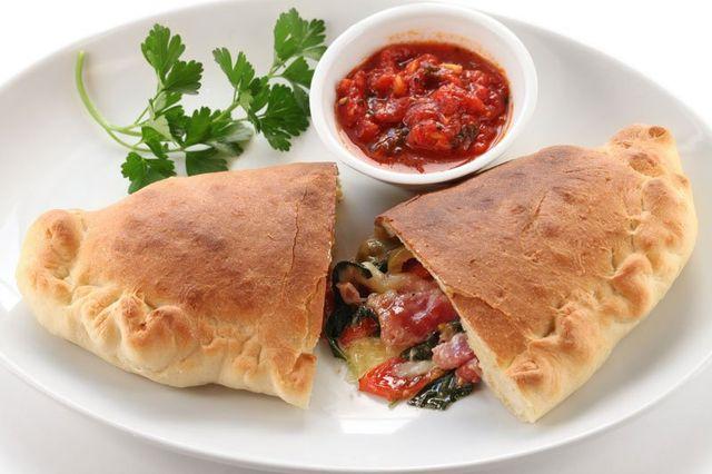 Piatto di calzone tagliato in due, ripieno con verdure , sugo di pomodoro fresco, foglie di prezzemolo