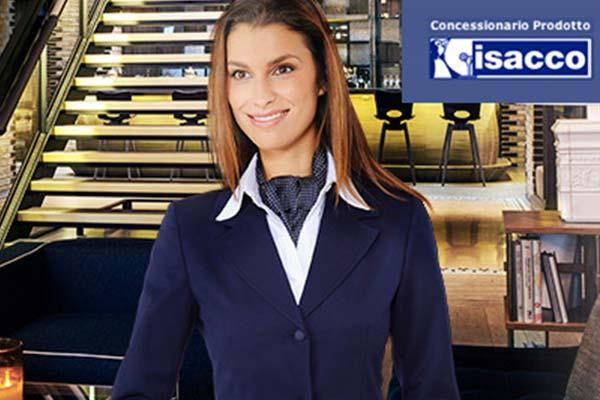 una donna con capelli castani indossa una camicetta bianca e un completo blu mentre si trova in un salone di esposizione