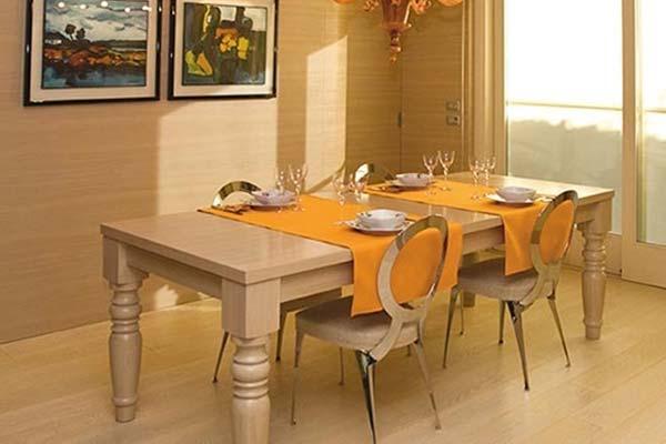 esposizione di un tavolo in legno chiaro, delle sedie, due quadri sul muro e un lampadario sul soffitto
