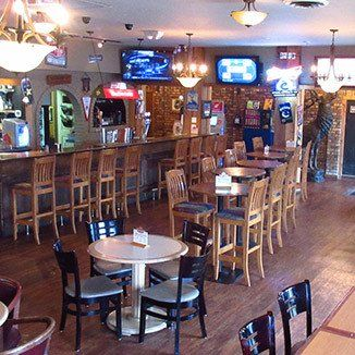 Photo of Bucky's Taphouse dinning room and bar, with flat screen tv's on a brick wall