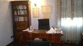 vista interna di una stanza con tavolo in legno, sedia e libreria in legno