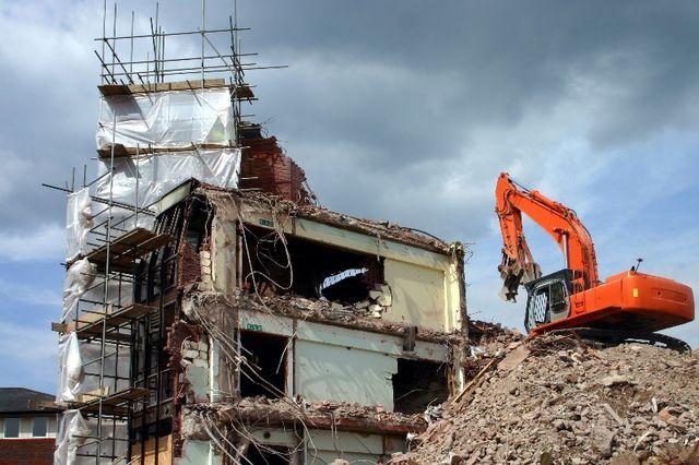 backhoe sitting on top of debris next to a demolition site